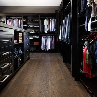 Imagen de armario vestidor unisex, clásico renovado, extra grande, con armarios con paneles empotrados, puertas de armario negras, suelo de madera oscura y suelo marrón