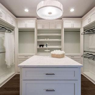 Diseño de vestidor clásico renovado, grande, con armarios estilo shaker, puertas de armario blancas, suelo de madera oscura y suelo marrón