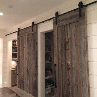 Cette photo montre un dressing nature neutre avec un placard sans porte, des portes de placard blanches et un sol en bois brun.
