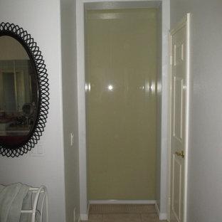 Diseño de vestidor unisex, moderno, de tamaño medio, con armarios tipo vitrina, puertas de armario grises, moqueta y suelo beige
