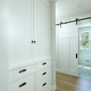 Diseño de armario unisex, campestre, pequeño, con armarios con paneles empotrados, puertas de armario blancas, suelo de madera clara y suelo marrón