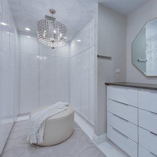 タンパの男女兼用コンテンポラリースタイルのおしゃれなウォークインクローゼット (フラットパネル扉のキャビネット、白いキャビネット、白い床) の写真