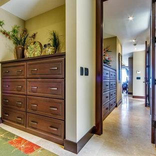 Mittelgroßes, Neutrales Tropisches Ankleidezimmer mit Ankleidebereich, profilierten Schrankfronten, braunen Schränken und Travertin in Hawaii