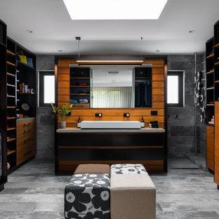 Diseño de vestidor unisex, contemporáneo, con puertas de armario de madera oscura y suelo gris