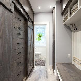 Idées déco pour un dressing bord de mer neutre et de taille moyenne avec des portes de placard en bois sombre, un sol en carrelage de porcelaine et un placard à porte plane.