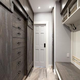 Maritim inredning av ett mellanstort walk-in-closet för könsneutrala, med skåp i mörkt trä, klinkergolv i porslin och släta luckor