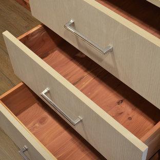 Idee per una piccola cabina armadio unisex stile marino con ante lisce, ante in legno chiaro e pavimento in legno massello medio