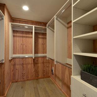 Idée de décoration pour un petit dressing marin neutre avec un placard à porte plane, des portes de placard en bois clair et un sol en bois brun.