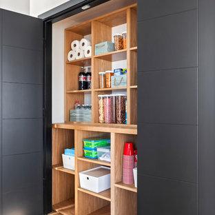 Idee per un armadio o armadio a muro unisex contemporaneo di medie dimensioni con nessun'anta, ante marroni e pavimento in legno massello medio