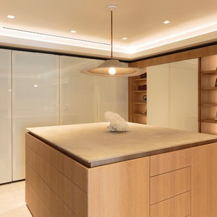 Dressing room - large contemporary gender-neutral light wood floor and beige floor dressing room idea in Los Angeles with flat-panel cabinets and medium tone wood cabinets