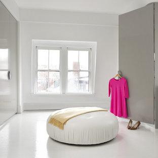 Imagen de armario y vestidor moderno, grande, con armarios con paneles lisos, puertas de armario grises, suelo de madera pintada y suelo blanco