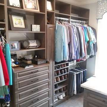 Beautiful Master Closet with island and unique jewelry cabinet