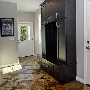 Immagine di una cabina armadio unisex moderna di medie dimensioni con ante lisce, ante nere e pavimento marrone