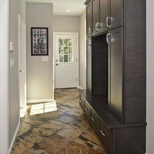 Foto di una cabina armadio unisex minimalista di medie dimensioni con ante lisce, ante nere e pavimento marrone