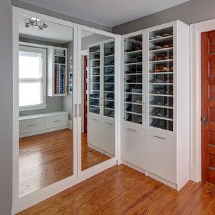 Foto di un armadio o armadio a muro unisex chic di medie dimensioni con ante di vetro, ante bianche, pavimento in legno massello medio e pavimento marrone