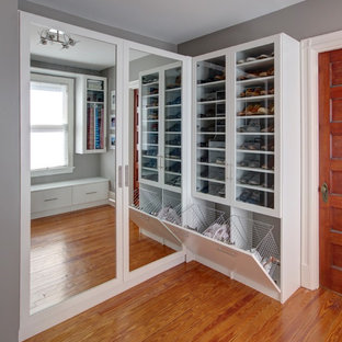 Inspiration for a mid-sized transitional gender-neutral walk-in wardrobe in New York with glass-front cabinets, white cabinets, medium hardwood floors and brown floor.