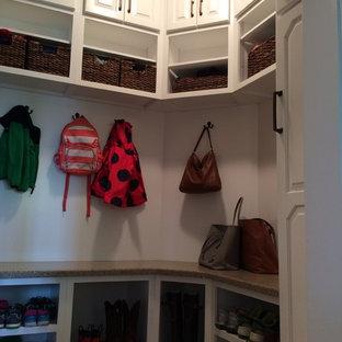 Ispirazione per una cabina armadio unisex classica di medie dimensioni con ante con bugna sagomata, ante in legno chiaro e pavimento in terracotta