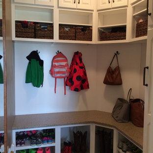 Cette photo montre un dressing chic de taille moyenne et neutre avec un placard avec porte à panneau surélevé, des portes de placard en bois clair et un sol en carreau de terre cuite.