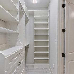 Imagen de armario vestidor unisex, clásico, de tamaño medio, con armarios estilo shaker, puertas de armario blancas, suelo de baldosas de porcelana y suelo gris