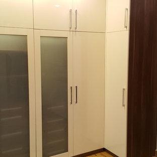 Foto di un grande spazio per vestirsi unisex minimalista con ante di vetro, ante in legno scuro, pavimento in laminato e pavimento giallo