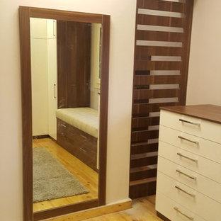 Exempel på ett stort modernt omklädningsrum för könsneutrala, med luckor med glaspanel, skåp i mellenmörkt trä, laminatgolv och gult golv