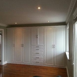 Imagen de armario unisex, clásico, grande, con armarios con paneles con relieve, puertas de armario blancas y suelo de madera en tonos medios