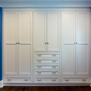 Idée de décoration pour un placard dressing design de taille moyenne et neutre avec un placard à porte shaker, des portes de placard blanches, un sol en bois brun et un sol marron.