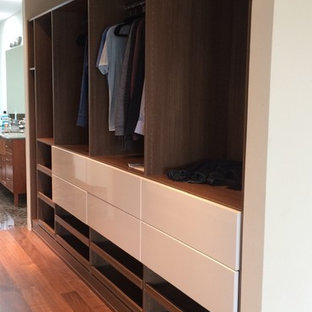 Design ideas for a mid-sized midcentury gender-neutral walk-in wardrobe in Seattle with flat-panel cabinets and medium wood cabinets.