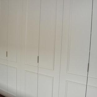Imagen de vestidor bohemio, grande, con puertas de armario blancas y suelo de madera oscura