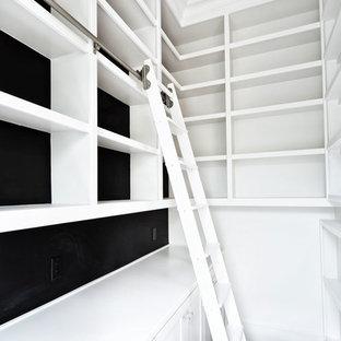 Imagen de armario vestidor unisex, moderno, grande, con armarios con paneles empotrados, puertas de armario blancas y suelo de madera clara