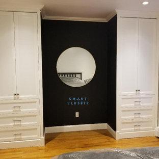 Immagine di un piccolo spazio per vestirsi unisex stile shabby con ante con bugna sagomata, ante bianche, pavimento in legno massello medio e pavimento marrone