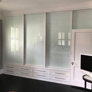 Idée de décoration pour un petit placard dressing design neutre avec un placard à porte shaker, des portes de placard blanches, sol en stratifié et un sol noir.