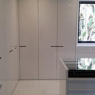 Ispirazione per una grande cabina armadio unisex moderna con ante lisce, ante bianche, pavimento in marmo e pavimento bianco