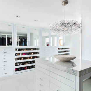 Inspiration for a large 1960s gender-neutral walk-in closet remodel in Los Angeles with flat-panel cabinets and white cabinets