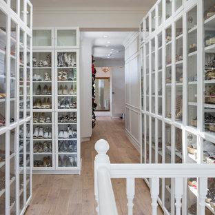 Esempio di una cabina armadio per donna stile marinaro con ante di vetro, ante bianche, pavimento in legno massello medio e pavimento marrone