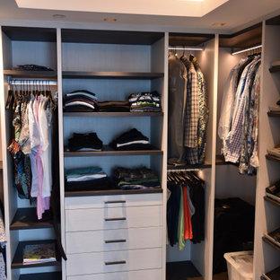 Imagen de armario vestidor de hombre, minimalista, de tamaño medio, con armarios abiertos, puertas de armario de madera clara, suelo de baldosas de porcelana y suelo azul