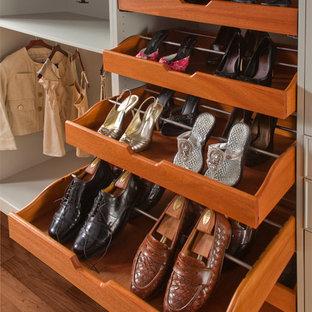 Imagen de armario vestidor unisex, bohemio, grande, con armarios abiertos, puertas de armario blancas y suelo de madera en tonos medios