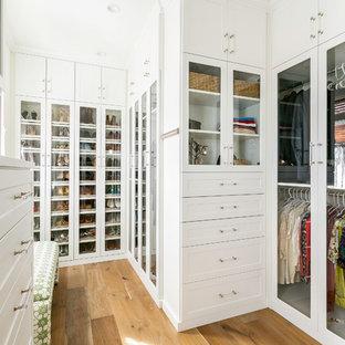 Foto di uno spazio per vestirsi unisex tradizionale con ante di vetro, ante bianche, pavimento in legno massello medio e pavimento marrone