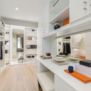 Photo of a large contemporary walk-in wardrobe for women in New York with flat-panel cabinets, white cabinets, light hardwood flooring and beige floors.