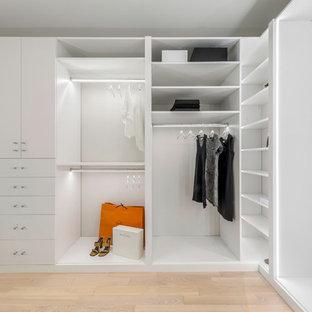 Esempio di una grande cabina armadio per donna design con ante lisce, ante bianche, parquet chiaro e pavimento beige