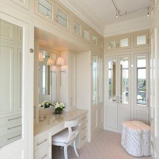 Cette image montre un grand dressing room design neutre avec un placard avec porte à panneau encastré, des portes de placard blanches et moquette.