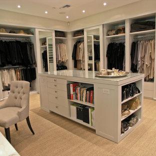 Modelo de vestidor unisex, contemporáneo, de tamaño medio, con armarios abiertos, puertas de armario beige y moqueta