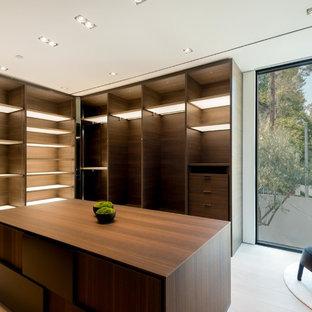 Foto di un'ampia cabina armadio unisex moderna con nessun'anta, ante in legno bruno, pavimento in laminato e pavimento beige