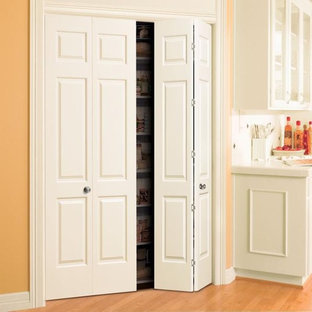 World-inspired walk-in wardrobe in Tampa with open cabinets, white cabinets and light hardwood flooring.