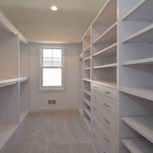 Пример оригинального дизайна: огромная гардеробная комната унисекс в стиле кантри с желтыми фасадами, ковровым покрытием и серым полом