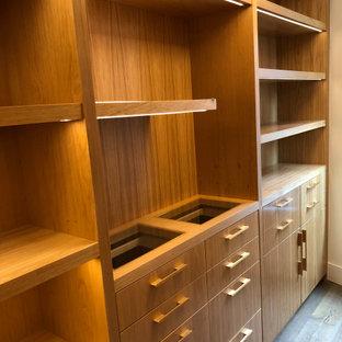 Esempio di una grande cabina armadio moderna con ante lisce e ante marroni