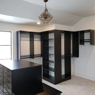 Ejemplo de armario vestidor unisex, clásico renovado, con armarios con paneles lisos, puertas de armario negras, moqueta y suelo beige