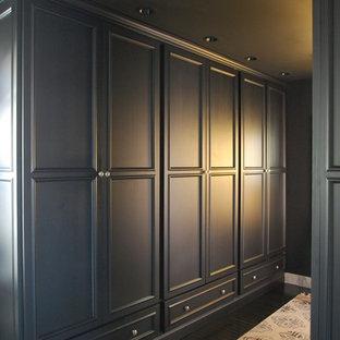 Idee per una cabina armadio unisex minimal con ante con riquadro incassato, ante nere e parquet scuro