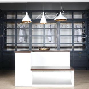 Ejemplo de vestidor unisex, moderno, extra grande, con armarios con paneles empotrados, puertas de armario grises y suelo de madera clara