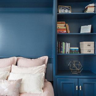 Imagen de armario y vestidor unisex, tradicional renovado, de tamaño medio, con armarios con paneles empotrados, puertas de armario azules, suelo laminado y suelo marrón